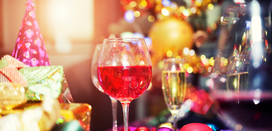 Red champagne glasses on table with gift boxes and party accessories with blurred bokeh light background. Merry Christmas and Happy New Year celebration concept.